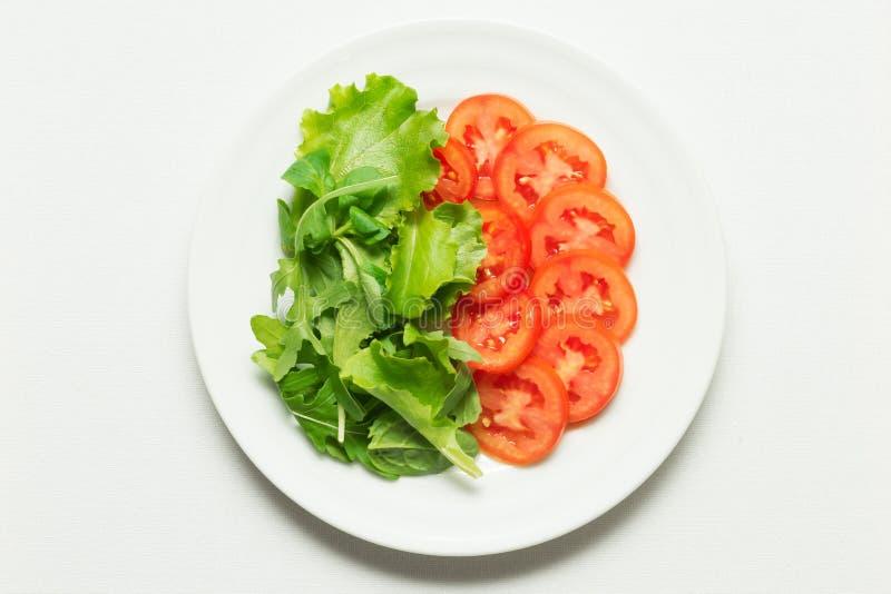 Lattuga e pomodori sopra il piatto bianco immagini stock libere da diritti