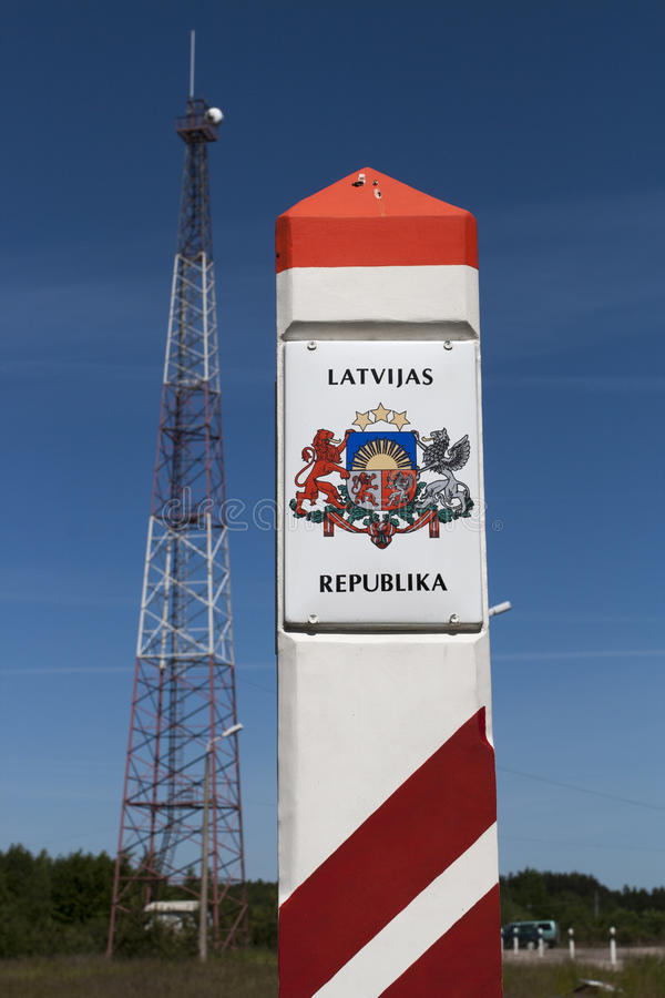 Latvia country border sign. Between Latvia and Lithuania with coat of arms and flag royalty free stock photo