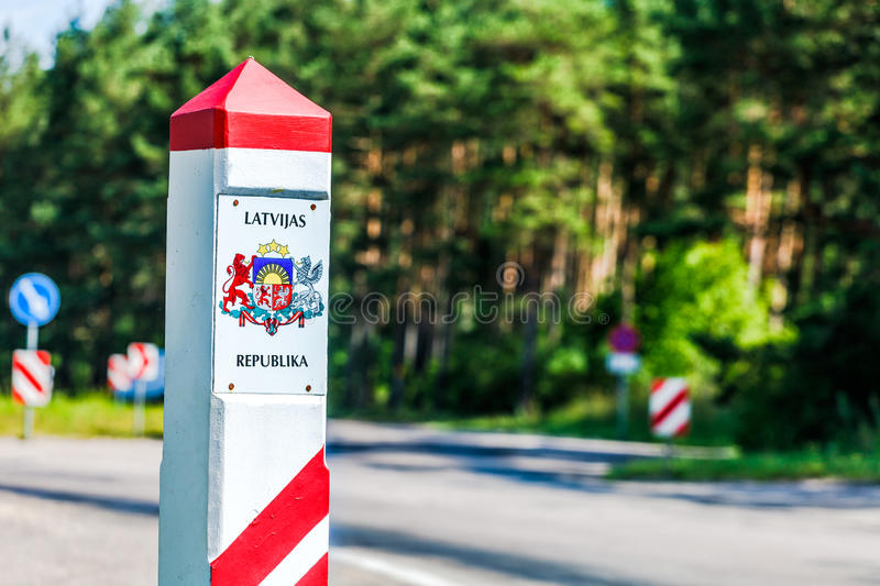 Latvia country border sign. Between Latvia and Lithuania with coat of arms and flag royalty free stock image