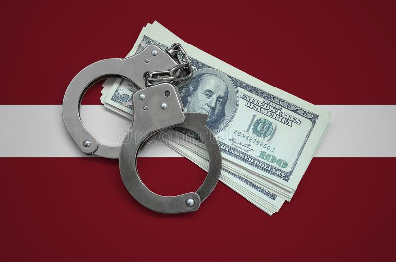 Latvia flag with handcuffs and a bundle of dollars. Currency corruption in the country. Financial crimes.  royalty free stock photos