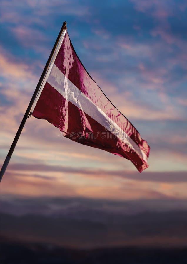 Latvia flag, Latvian flag waving on sky at dusk royalty free stock photography