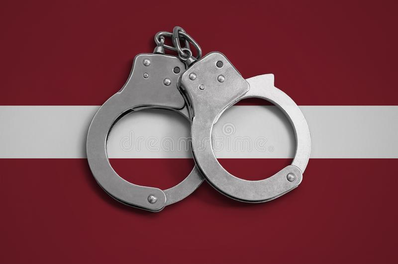 Latvia flag and police handcuffs. The concept of observance of the law in the country and protection from crime.  royalty free stock images
