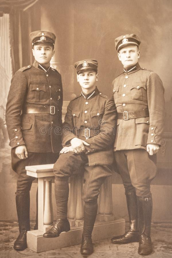Latvia - 1930s: An antique photo shows three soldiers posing in front of camera stock image