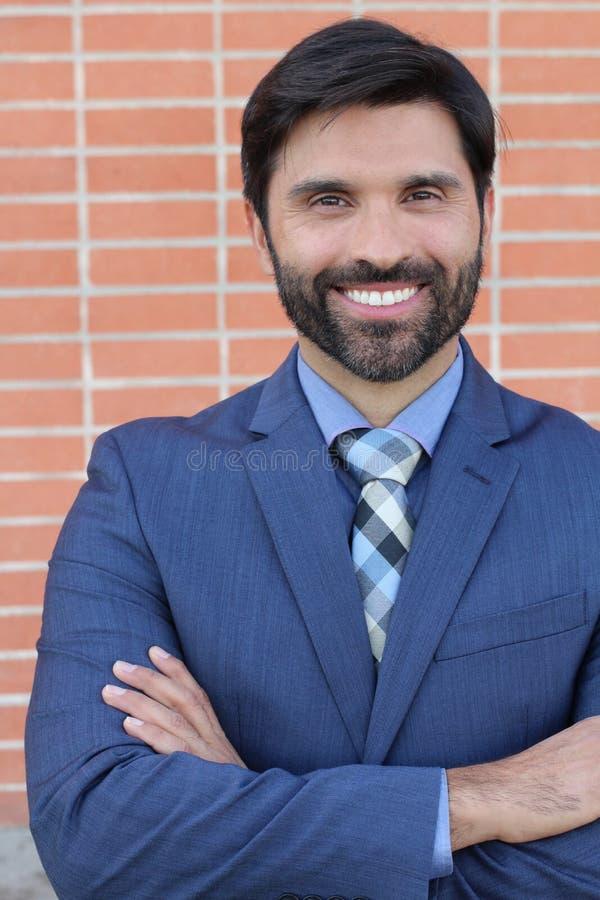 Latyno-amerykański biznesowy mężczyzna krzyżuje jego ono uśmiecha się i ręki odizolowywał na ściana z cegieł tle obrazy stock