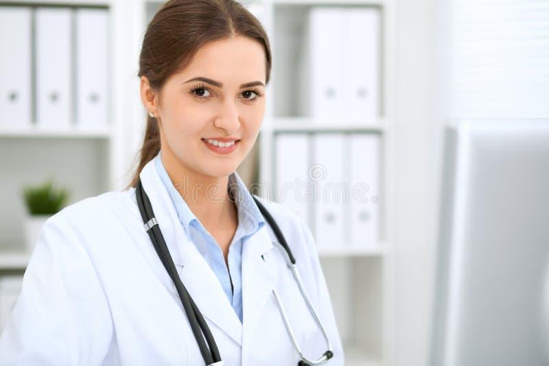 Latyno-amerykański kobiety lekarki obsiadanie przy stołem i działanie komputerem przy szpitalnym biurem Terapeuta lub lekarz zdjęcia stock