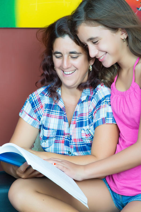 Latynos macierzysty i jej córka czyta książkę obraz stock