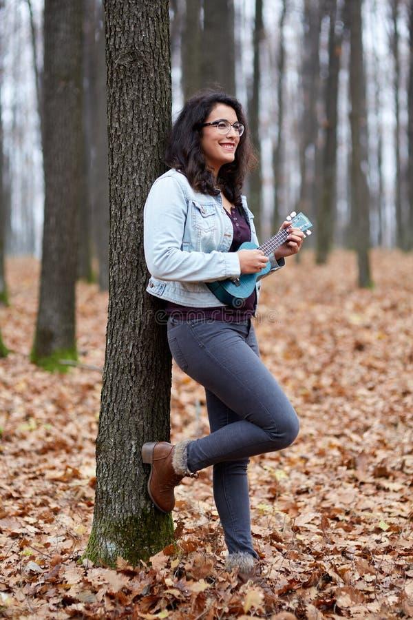 Latynoska dziewczyna bawić się ukulele zdjęcia royalty free