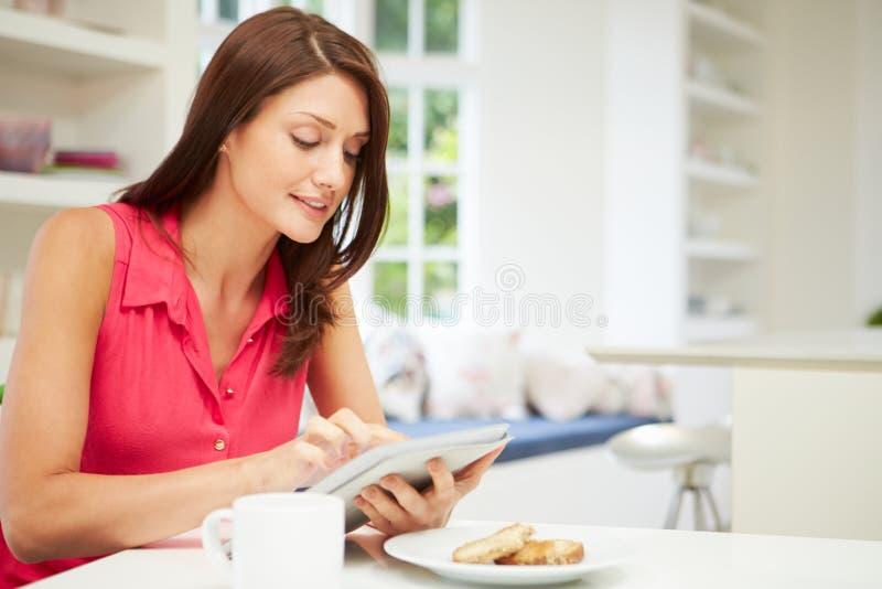 Latynoska kobieta Używa Cyfrowej pastylkę W kuchni obraz royalty free