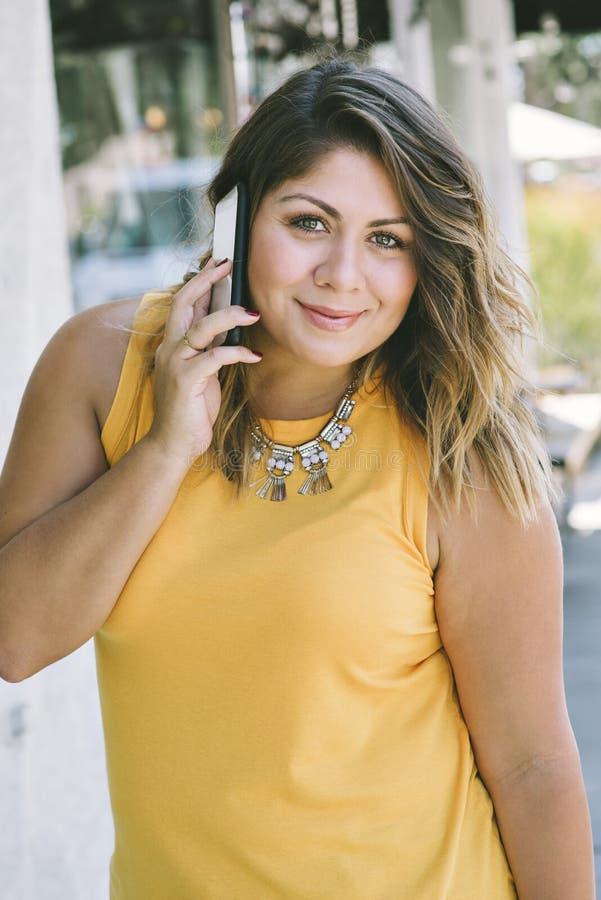 Latynoska młoda dziewczyna Trzyma telefon komórkowego Jej ucho Podczas gdy Uśmiechnięty i Szczęśliwa Millennial moda Przypadkowa zdjęcie stock