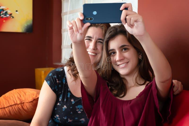 Latynoska nastoletnia dziewczyna i jej matka bierze selfie w domu obrazy stock