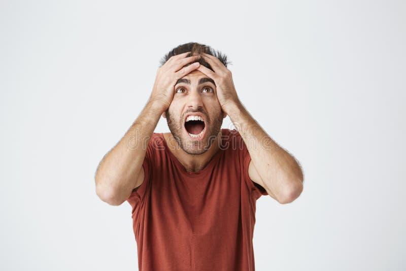 Latynoski beardy mężczyzna w czerwony koszulowy ekspresyjnym reaguje na złej wiadomości od pracy dostaje sikający o jego szefie N obraz stock