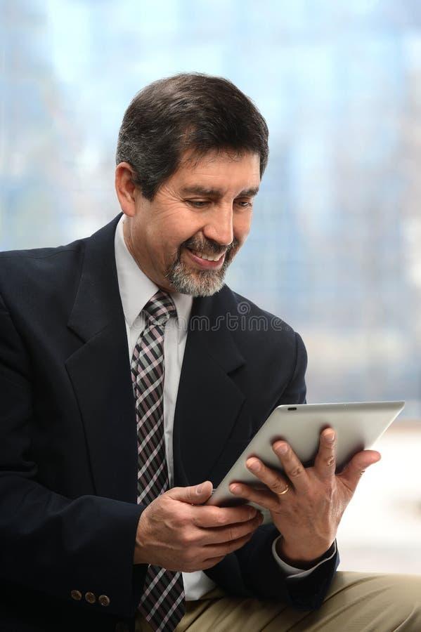 Latynoski biznesmen Używa Elecroni pastylkę obraz stock