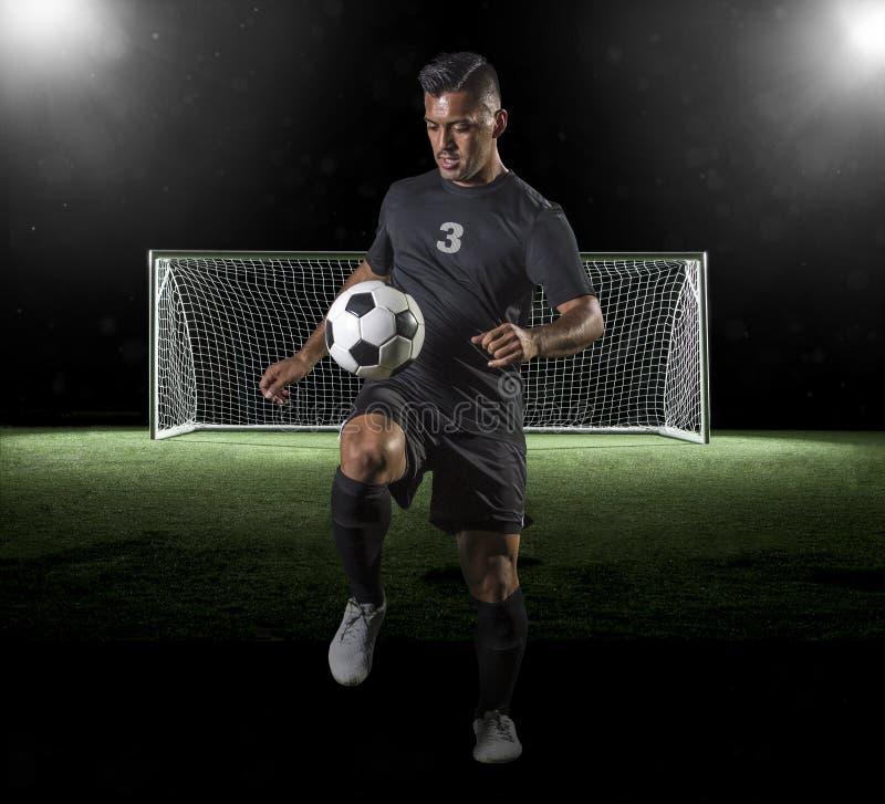 Latynoski gracz piłki nożnej bawić się piłkę nożną na ciemnym tle zdjęcie royalty free