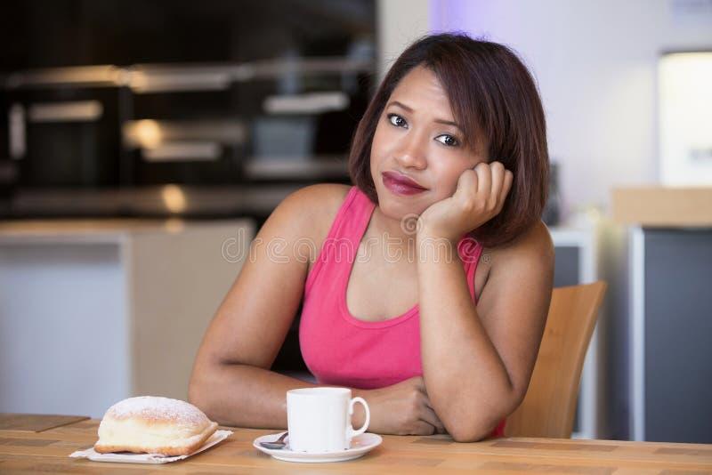 Latynoski kobiety obsiadanie przy stołowy patrzeć zanudzający obraz stock
