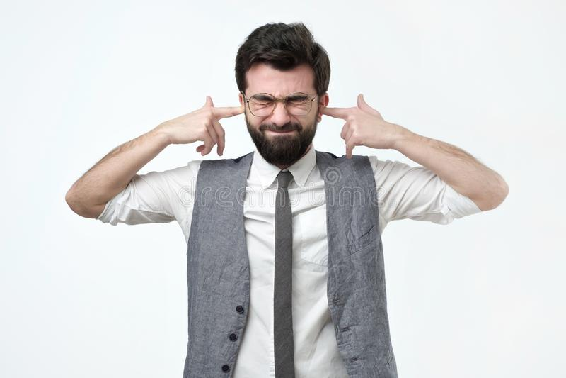 Latynoski mężczyzna czopuje ucho z palcami, ignoruje, utrzymań oczy zamykający, głośnego hałas lub muzykę obraz stock