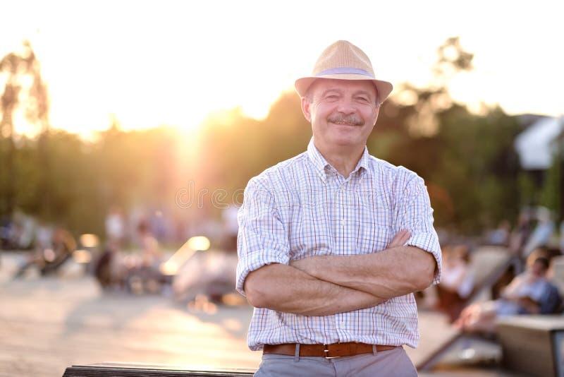 Latynoski mężczyzna ono uśmiecha się w lato kapeluszu z fałdowymi rękami patrzejący kamery pozycję na miasto parku zdjęcia royalty free