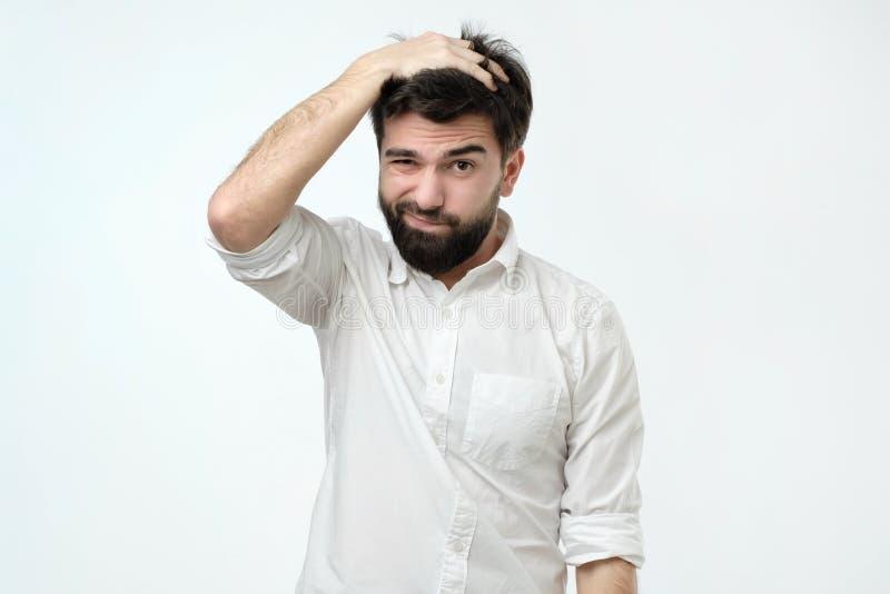 Latynoski mężczyzna patrzeje z intrygującym wyrażeniem z brodą, drapający głowę, być nieświadomy zdjęcia royalty free