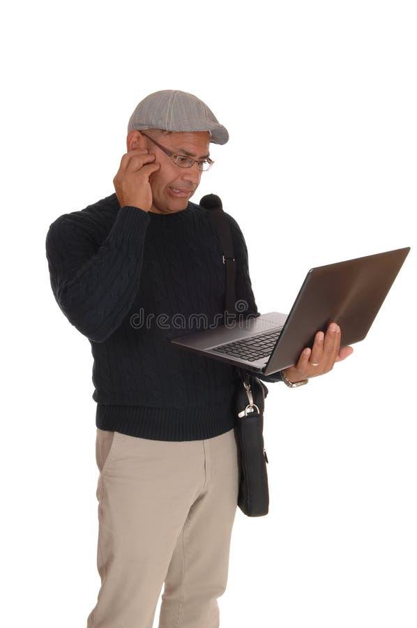 Latynoski mężczyzna pracuje na jego laptopie zdjęcie royalty free