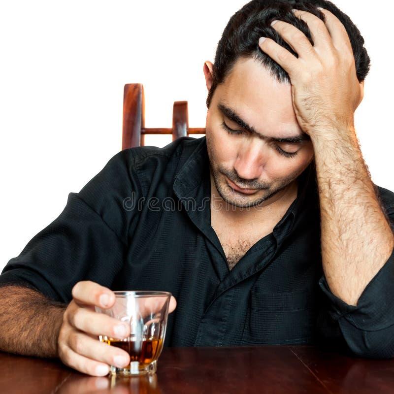 Latynoski mężczyzna trzyma alkoholicznego napój i cierpi migrenę zdjęcia stock