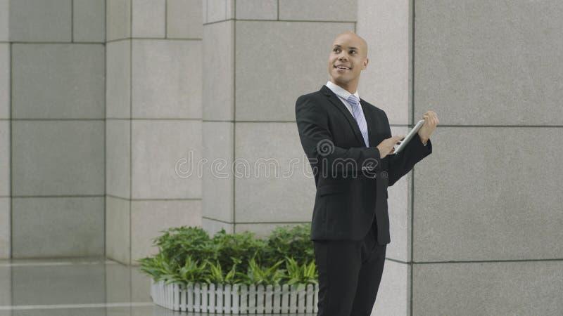 Latynoskiego biznesmena przyglądający up ono uśmiecha się obraz stock
