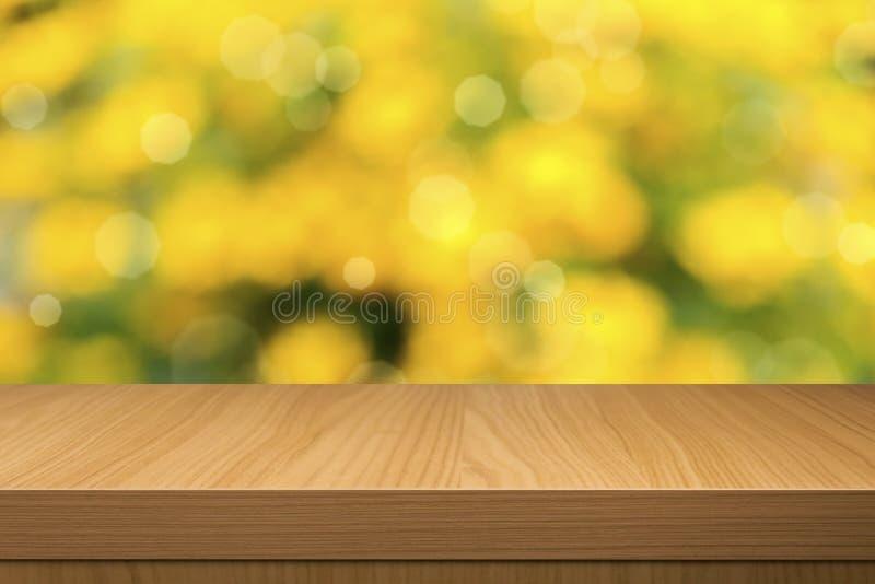 Laub bokeh Hintergrund mit leerem Holztisch lizenzfreie stockfotos