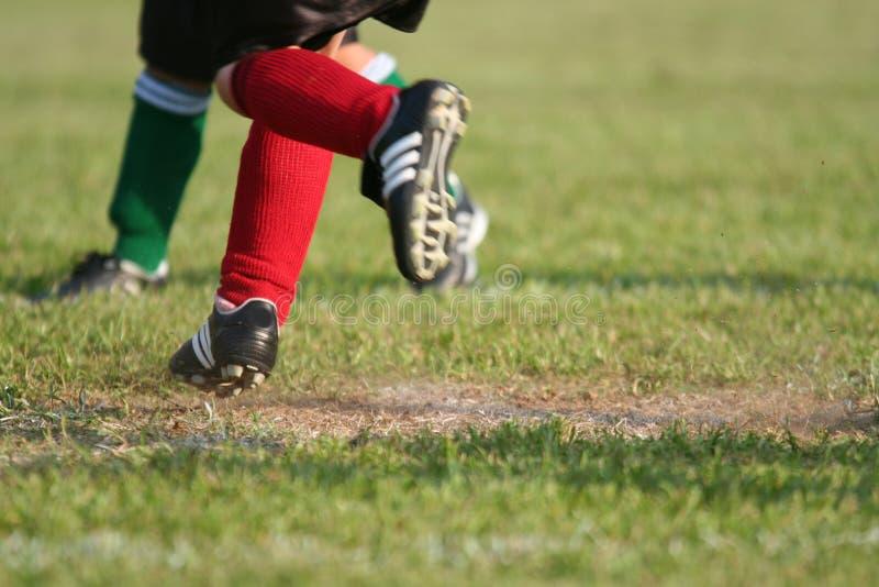 Laufen auf Fußballplatz lizenzfreie stockfotos