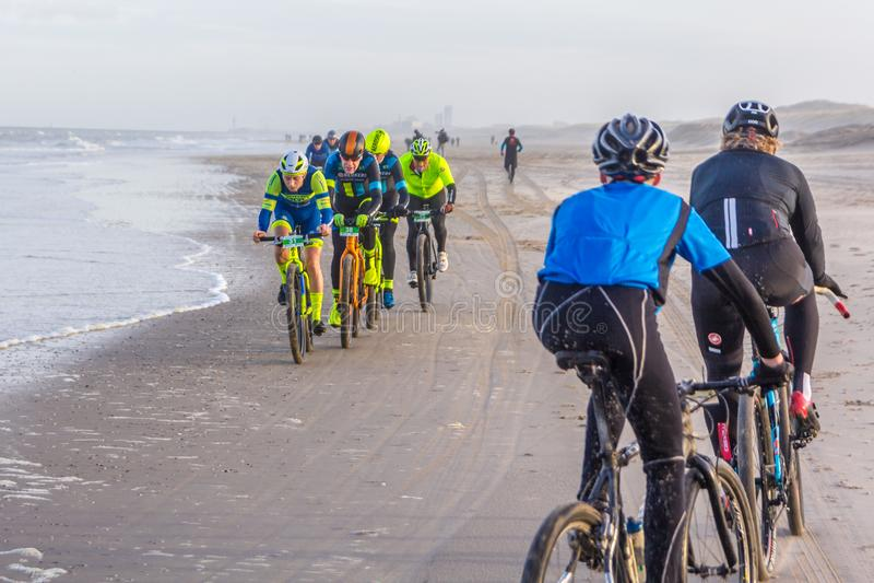 Laufen von Fahrradwettbewerbsreitern im Strand lizenzfreie stockfotos