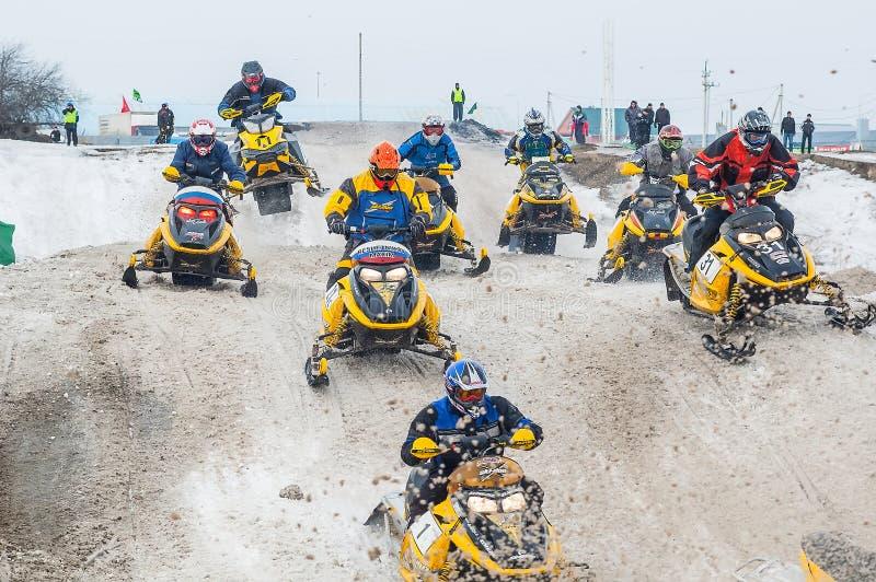 Laufen von Sportlern auf Schneemobil fahrung lizenzfreie stockfotos