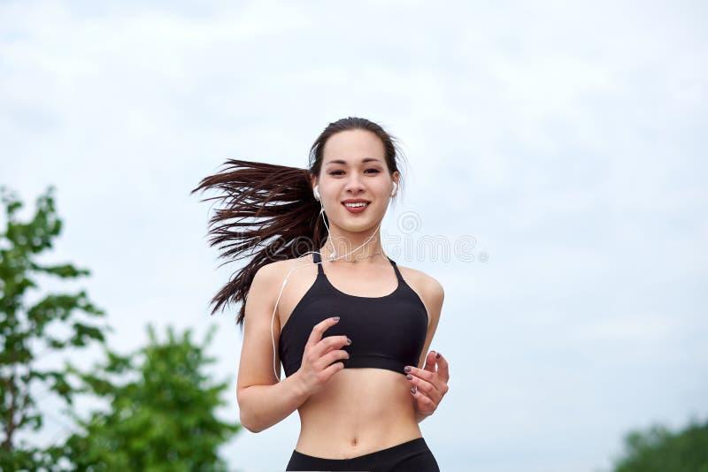 Laufende asiatische Athletenfrau Morgenr?tteln lizenzfreie stockfotografie