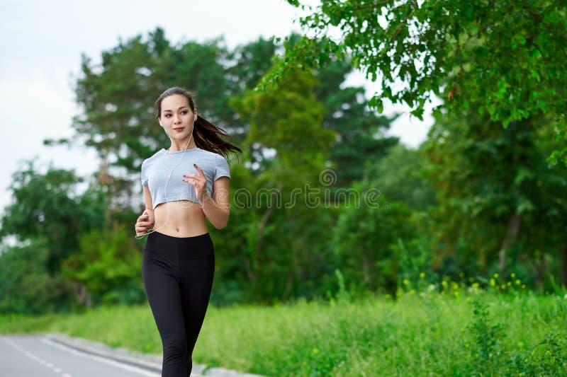 Laufende asiatische Frau auf Laufbahn Morgenr?tteln Das Athletentraining stockfotografie