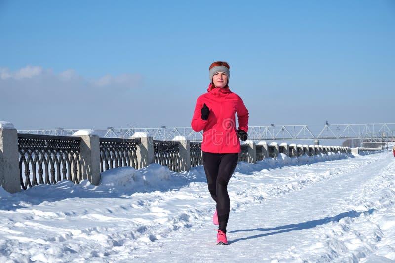 Laufende Athletenfrau, die während des Wintertrainings draußen im kalten Schneewetter sprintet Schließen Sie herauf das Zeigen vo stockfotos