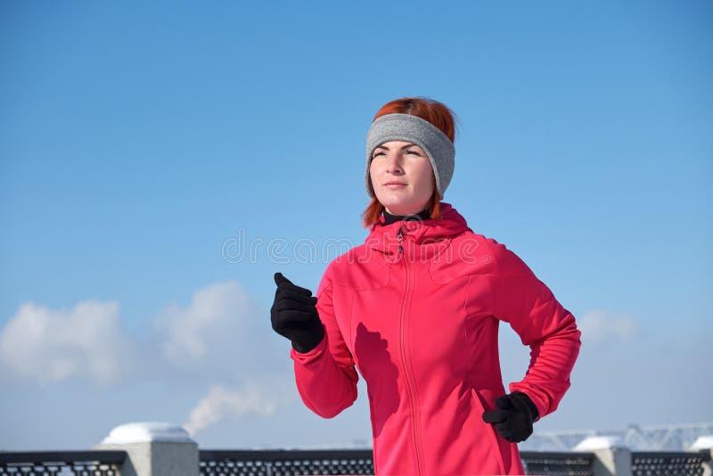 Laufende Athletenfrau, die während Wintertrainingsaußenseite I sprintet lizenzfreie stockfotografie