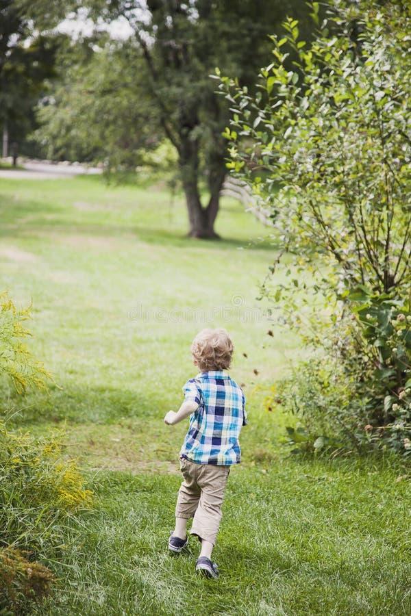 Laufende Außenseite des glücklichen Jungen lizenzfreie stockbilder