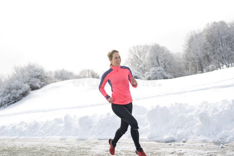 Laufende Frau der Eignung in der Wintersaison stockfoto