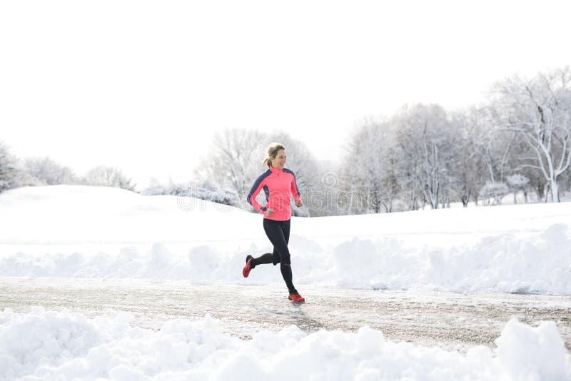 Laufende Frau der Eignung in der Wintersaison stockbild