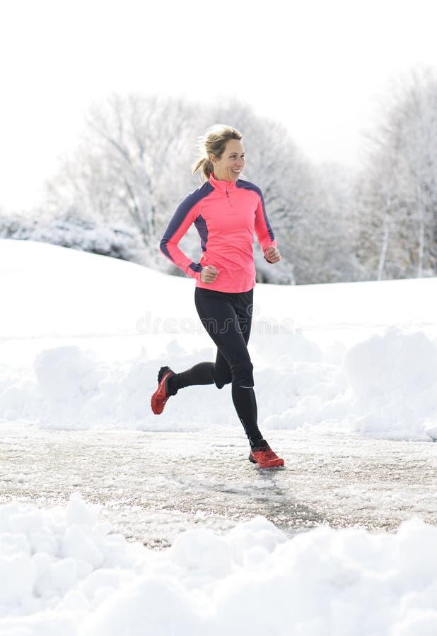 Laufende Frau der Eignung in der Wintersaison stockfotos