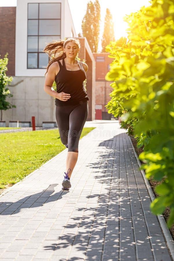 Laufende Frau in der schwarzen Sportausstattung auf dem Bürgersteig lizenzfreie stockfotografie