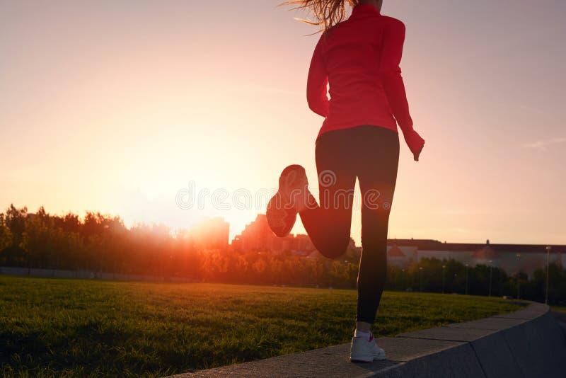 Laufende Frau des Athleten auf der Straße im Morgensonnenaufgangtraining für Marathon und Eignung lizenzfreie stockfotografie