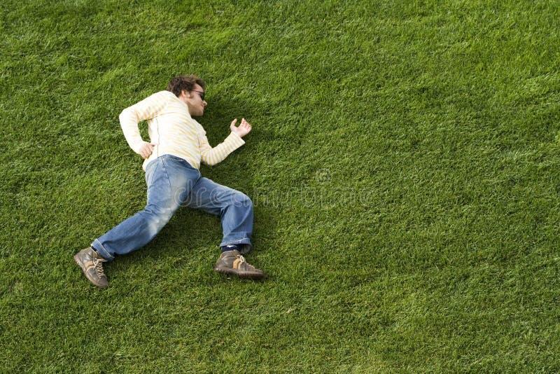 Laufende Niederlegung auf dem Gras lizenzfreie stockbilder