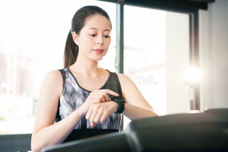 Laufende Tretmühle der schönen asiatischen Frau smartwatch Kontrollimpuls stockfotografie