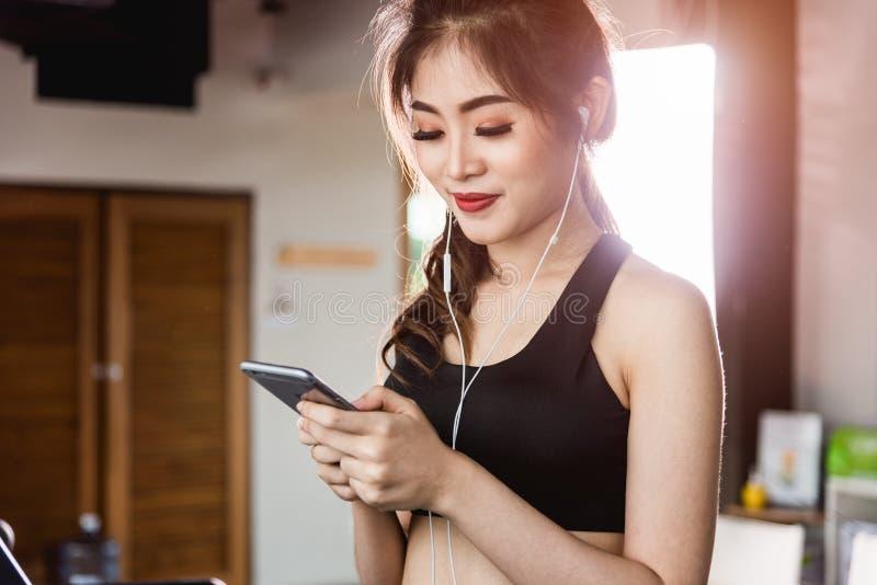 Laufende Tretmühle des Lebensstils der jungen Frau unter Verwendung des intelligenten Handys stockfoto