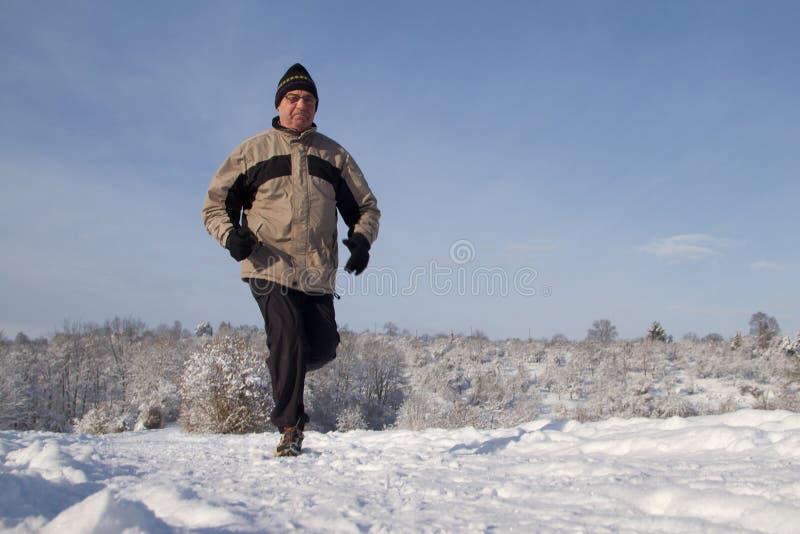 Laufender Älterer im Schnee stockbild