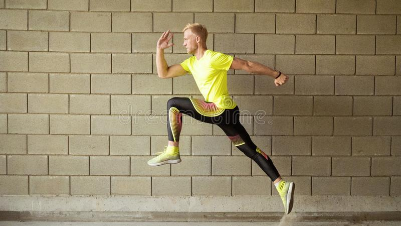 Laufender junger Mann, graue Wand auf Hintergrund stockbild