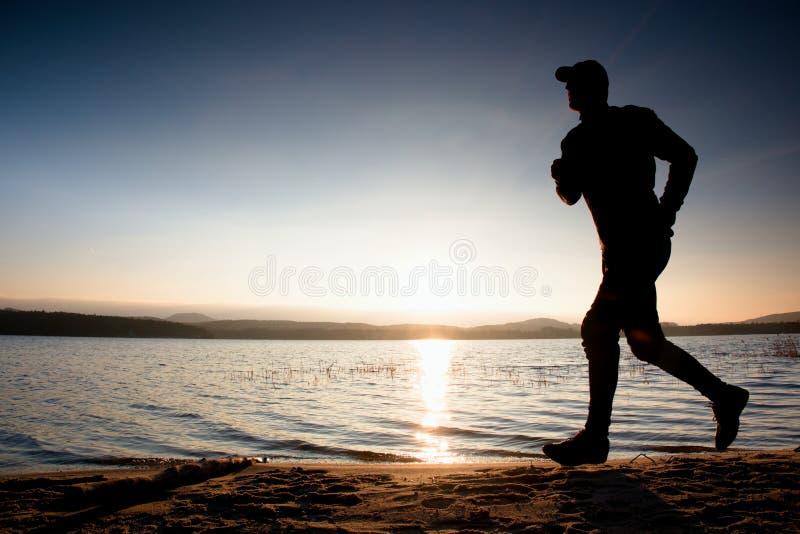 Laufender Mann auf Strand Sportler laufen in Baseball capr und rütteln Kerl während des Sonnenaufgangs lizenzfreies stockbild