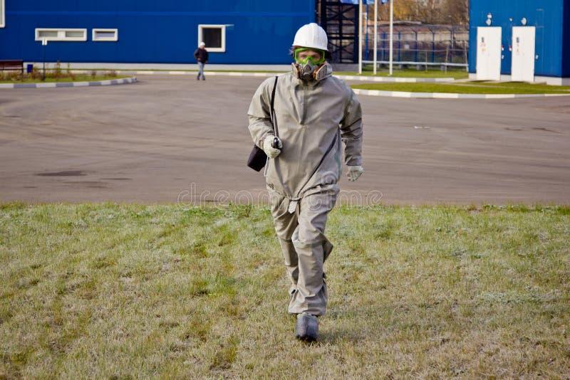 Laufender Mann in der Chemikalienschutzklage, im Sturzhelm und in der Gasmaske lizenzfreie stockbilder