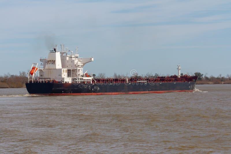 Laufendes Manövrieren des Bulkladungsschiffs im schlammigen Fluss stockbild