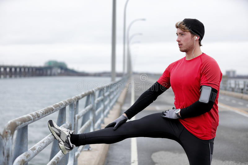 Laufendes Mannaufwärmen der Wintereignung, das Beine ausdehnt lizenzfreies stockfoto