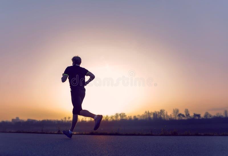 Laufendes Mannschattenbild in der Sonnenuntergangzeit stockfotografie
