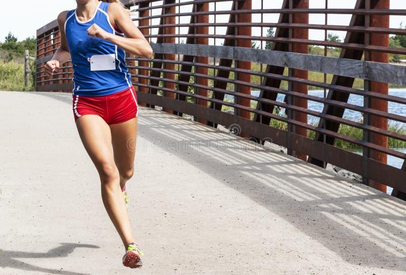Laufendes Rennen der Oberschülerinnen über einer Brücke lizenzfreies stockfoto