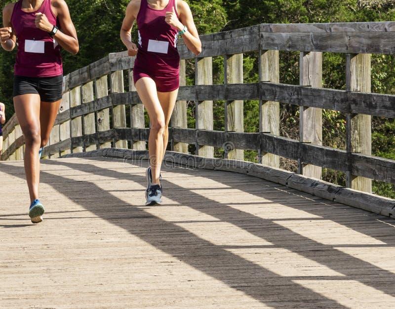 Laufendes Rennen von zwei Mädchen über hölzerner Brücke stockfotografie